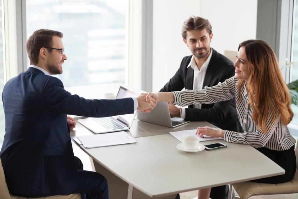 Businessman handshaking businesswoman making deal finishing group negotiations