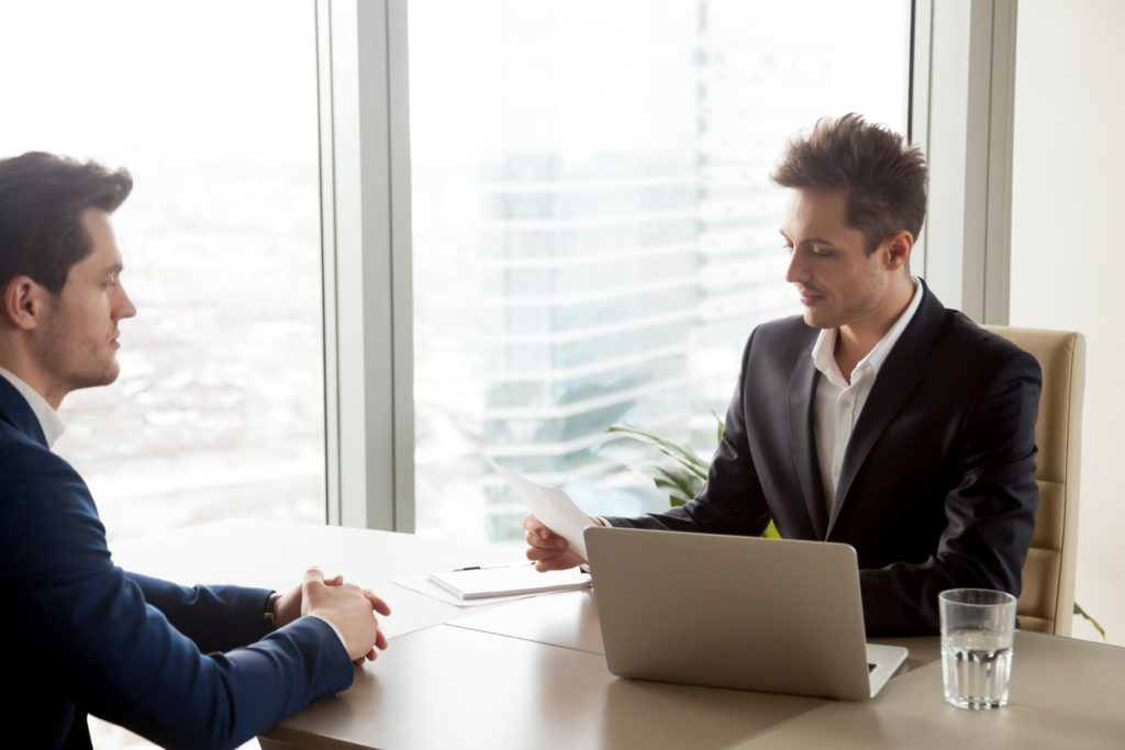Focused recruiter reviewing resume of male applicant during job interview